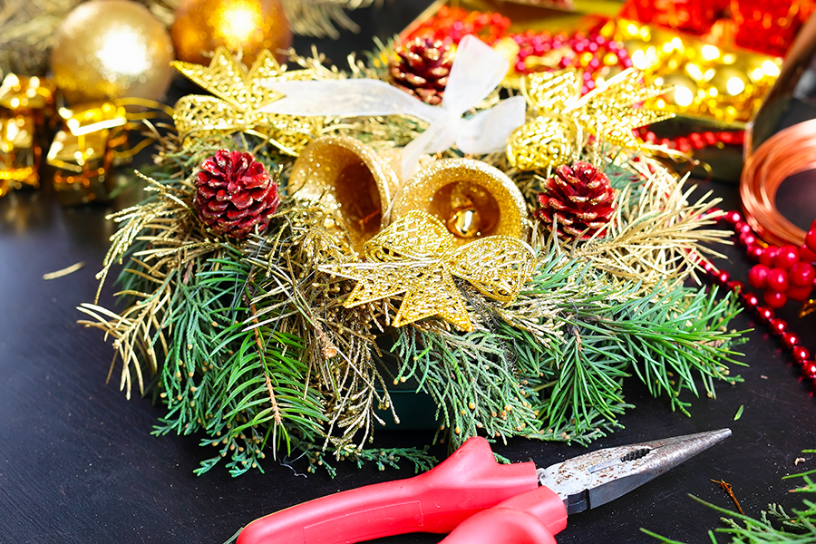 Decorating a red and gold Christmas wreath