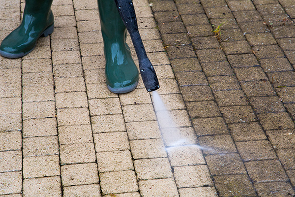 Pressure washing paving on patio with pressure washer